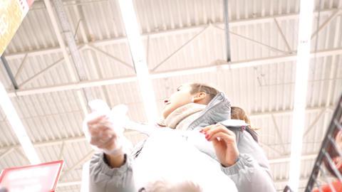 low angle shot girl ties plastic bag puts into cart Live Action