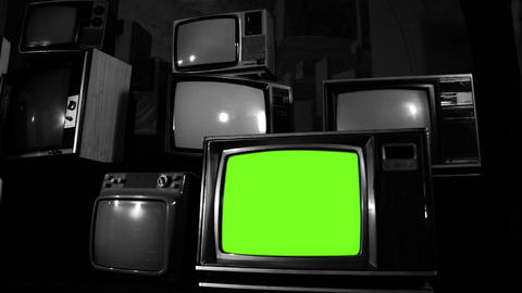 Old Tv Turning On Green Screen In A Pile Of Many Old Tvs. Black And White Tone Footage
