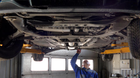 skilled garage worker examining lifted car Footage