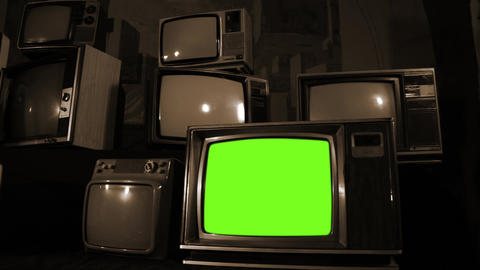 Old Tv Turning On Green Screen, In A Pile Of Many Old Tvs. Sepia Tone Live Action