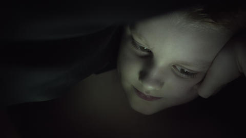 Little Boy Under The Covers At Night With A Digital Tablet Playing Game Archivo