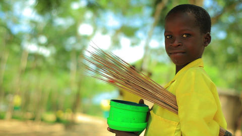 Little smiling Kenyan boy carrying straw and a bucket Footage