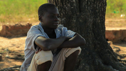 Kenyan boy sitting under a tree, thinking Footage