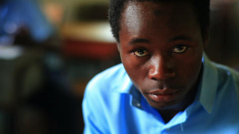 Kenyan student looks at the camera and his school work Footage