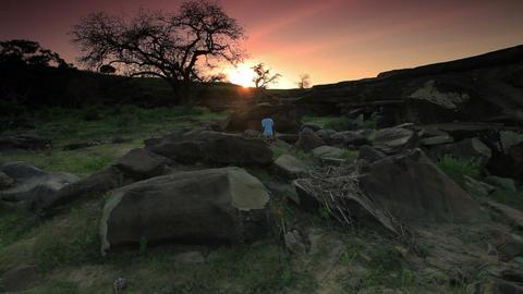 Kenyan boy walking over and around big rocks Footage