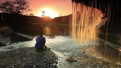 Child watching a waterfall and tossing a rock at sunset in Kenya, Africa Footage