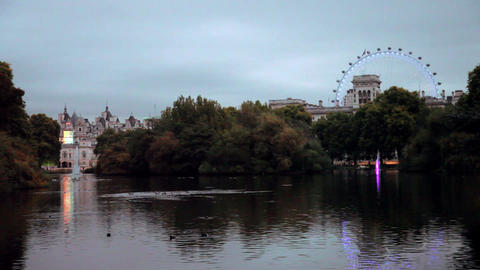 View from a bridge in a park overlooking a building and the London Eye in London Footage