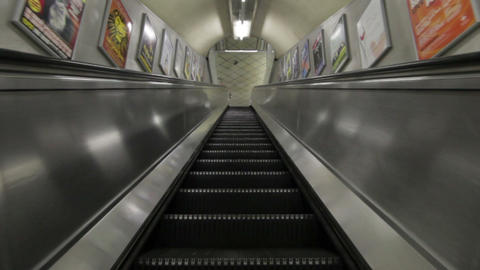 Low angle traveling view of escalator going downward in a building in London Footage