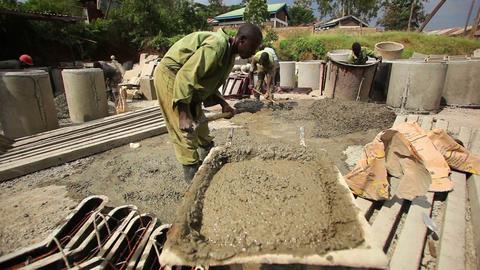 Man shoveling gravel into wheelbarrow Live Action