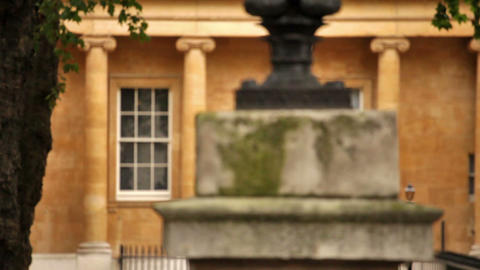 Stone pillar in front of an orange stone building with columns Footage