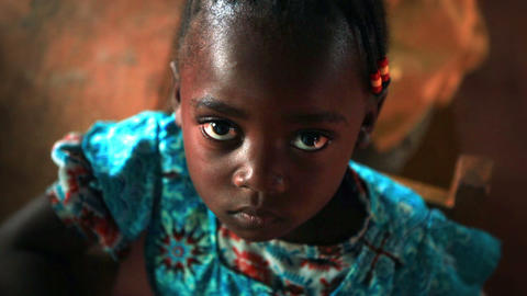 KENYA-C.2012 Little girl looks up at camera while recieving a snack in a Kenya,  Footage