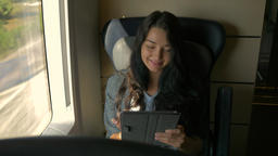 Young woman using her tablet computer while traveling by train. Travel Live Action