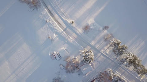 Aerial view of snowy neighborhood by a country road in winter Footage