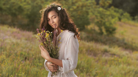 Natural beauty girl with bouquet of flowers outdoor in freedom enjoyment concept Footage