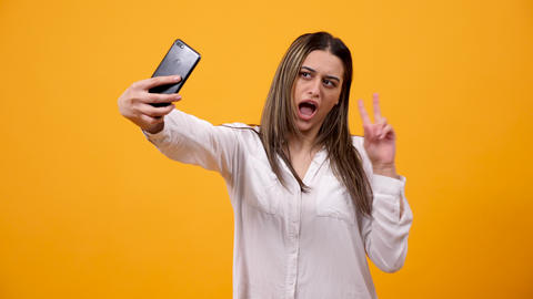 Smiling woman showing a peace sign and taking a selfie Live Action