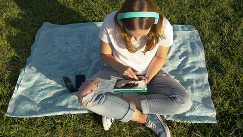 Top view of young female with gadgets and headphones in the park on green grass Live Action