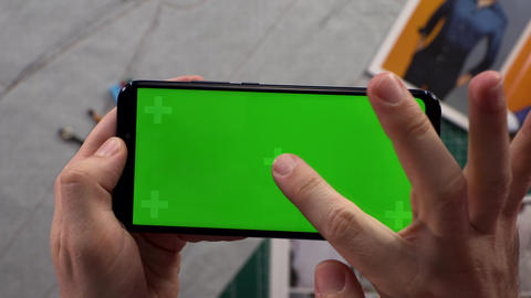 Close-up of men's hands holding smart phone with horizontal green screen in Footage