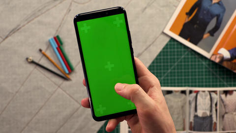 Close-up of men's hands holding smart phone vertical green screen in the Footage