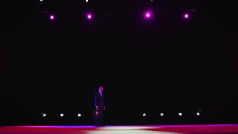 showman presents his show, spreading his hands to the sides. The guy in the Footage
