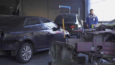 Indoor big car service workshop with modern equipment and crashed cars after an Footage