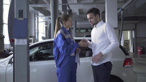 Female automobile specialist taking datas about car for inspection and friendly Live Action