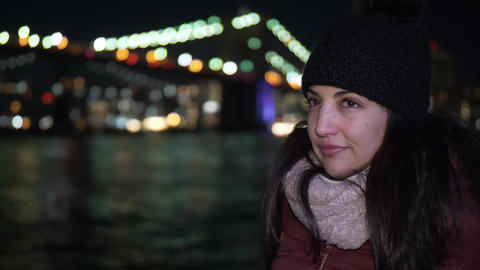Portrait shot of a young woman at Brooklyn Bridge by night Stock Video Footage