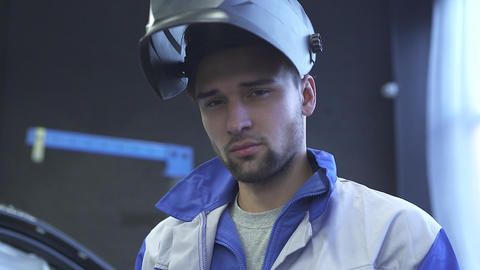Portrait of young specialist auto mechanic in welding helmet on the background Live Action