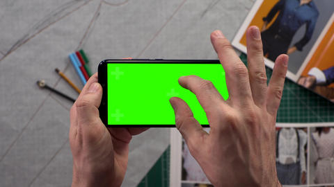 Close-up of men's hands holding smart phone with horizontal green screen in Live Action
