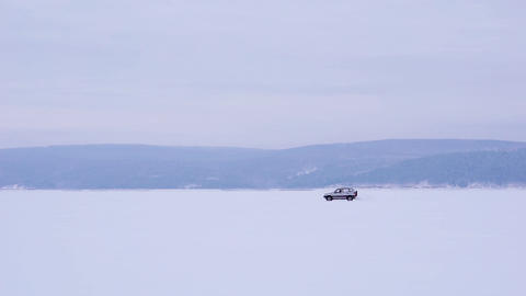 The car rides on the frozen lake. Winter daylight Footage