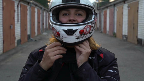 Woman rider putting on motorcycle helmet. On the garage street. Girl Ready for Footage