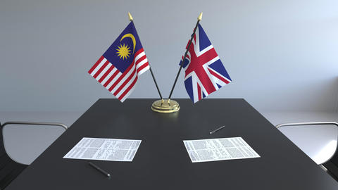 Flags of Malaysia and Great Britain and papers on the table. Negotiations and Live Action