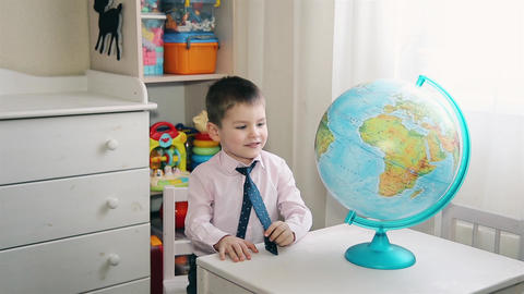 A little boy is looking for a place on the globe where he grew up Footage
