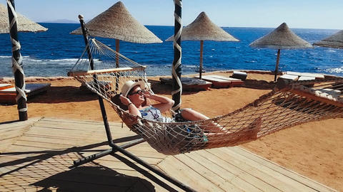 Woman chills in the hammock on the beach, vacation on the sea, relaxing on the Footage