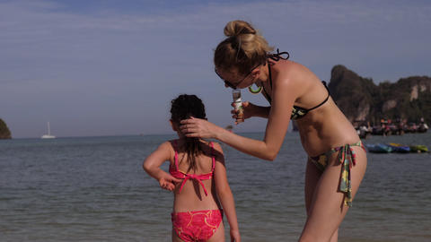 Mother smears little daughter back with sunscreen Footage