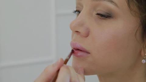 Makeup artist using brush for application lipstick on lips beautiful woman Footage