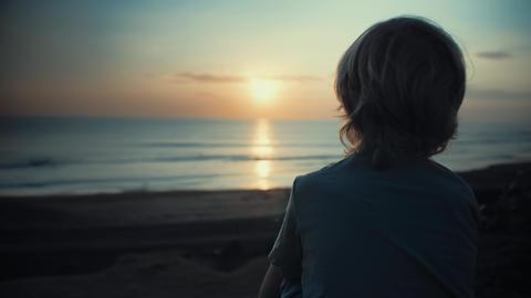 Child admiring beautiful sunset on shore Footage