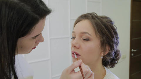 Makeup artist using brush for application lipstick on lips beautiful woman Live Action