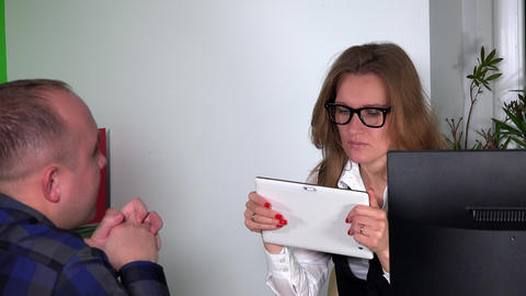 Pretty architect girl with glasses consulting customer man with tablet computer Footage