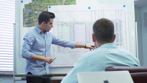 constructor presents drawing of new project to company head Footage