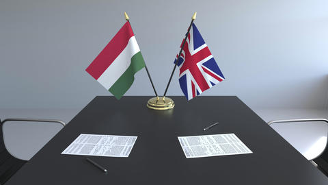 Flags of Hungary and Great Britain and papers on the table. Negotiations and Footage