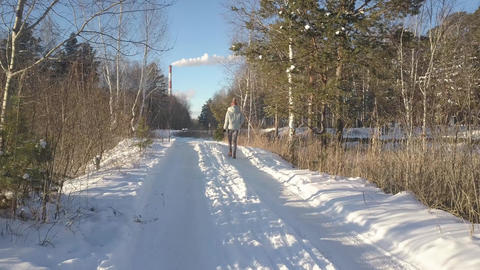 aerial low angle shot girl with pine walks along snowy track Footage