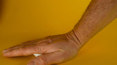 A man's hand crushes a white disposable plastic cup on a yellow background Footage