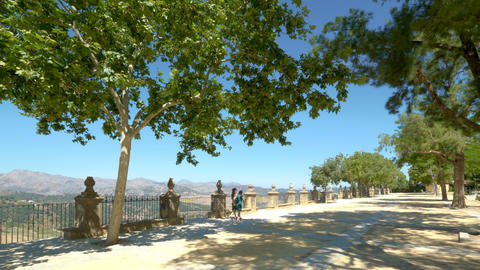 Tourists walking in the viewpoint of the gardens of Tajo de Ronda, in Ronda Spain on a sunny day Live Action