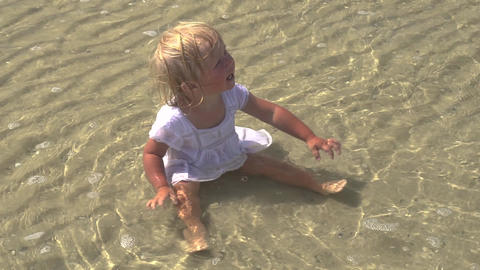 The child sits in the sea. Little girl sitting in the water on the beach Live Action