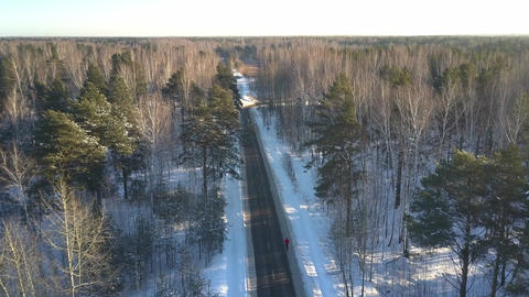 aerial motion above road with running man in winter forest GIF
