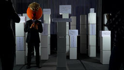 Big Head President Giving Speech Near Boxes With Current Political Issues Live Action