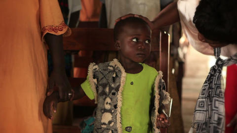 KENYA-C. A woman comforts a nervous child while adults sway around them in Kenya Footage