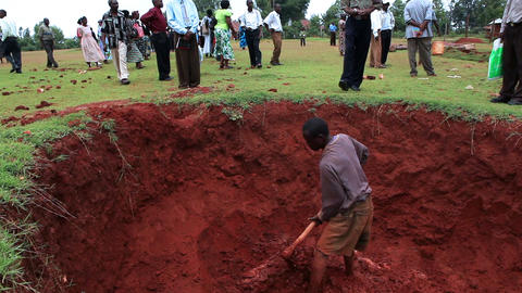 One man digging in a deep pit; others watch from above Footage