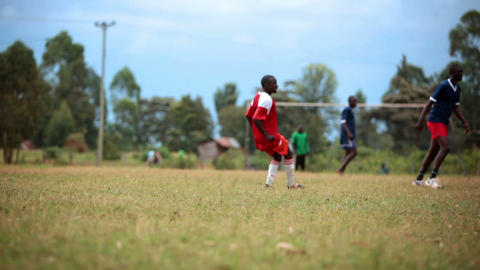 KENYA-C.2012 Two teams of African teens play an intense game of football in Keny Live Action