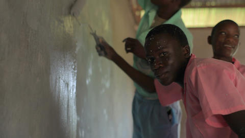 Children painting a wall in a village in Kenya Footage